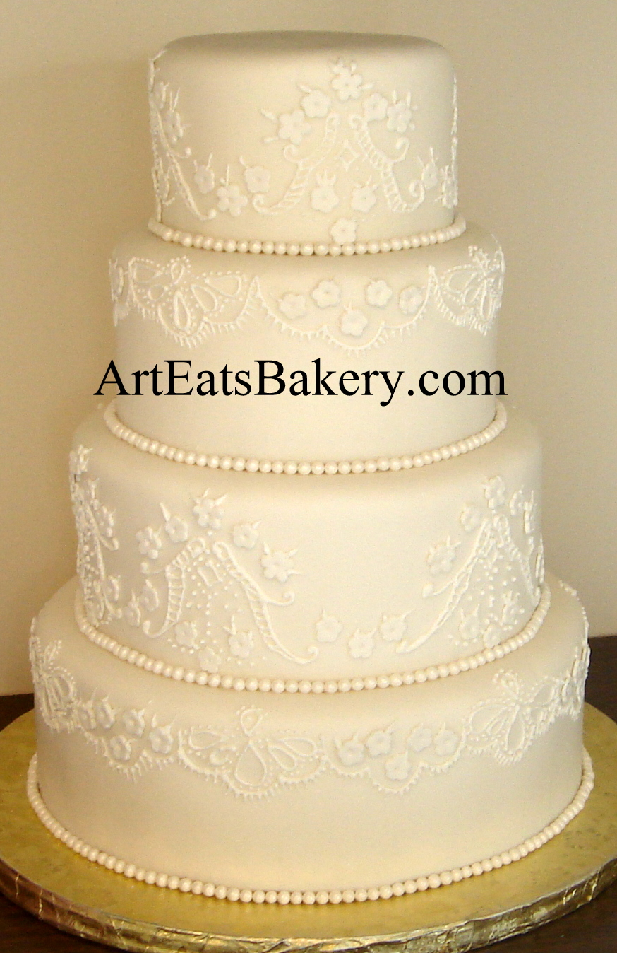 Elegant ivory fondant wedding cake with romantic white flower lace design and edible pearls.jpg