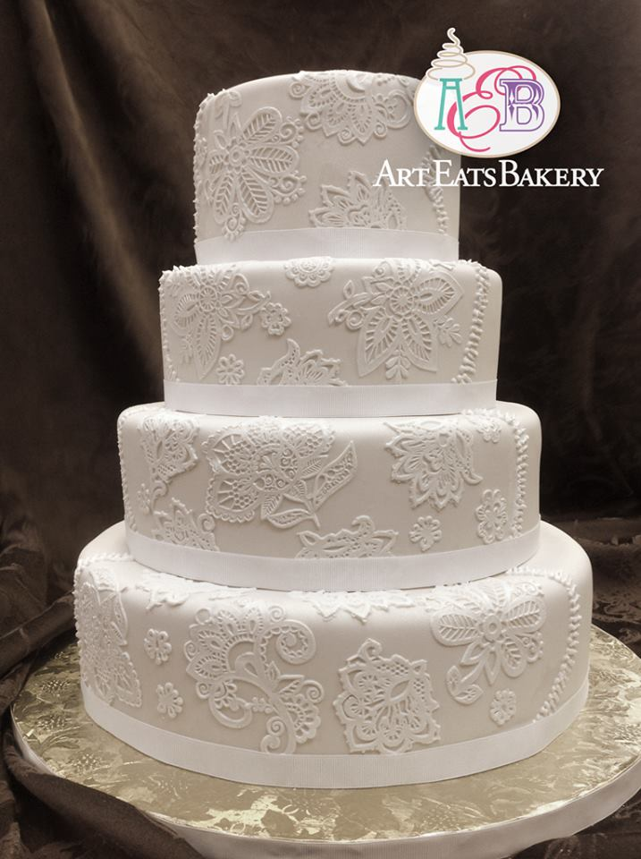 Romantic elegant 4 tier round wedding cake in ivory fondant embellished with delicate edible lace and classic ribbon trim..jpg