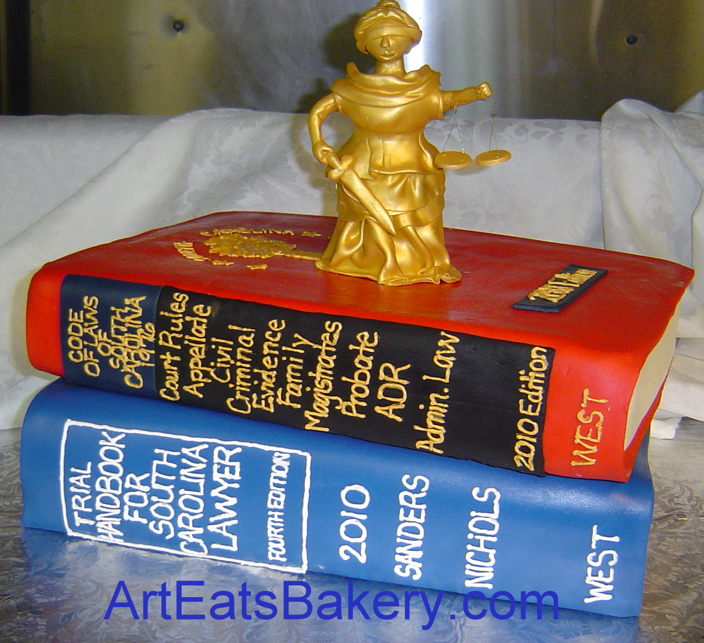 Lady Justice sugar figure on top of red and blue 3D law books custom 50th birthday cake for a lawyer.jpg
