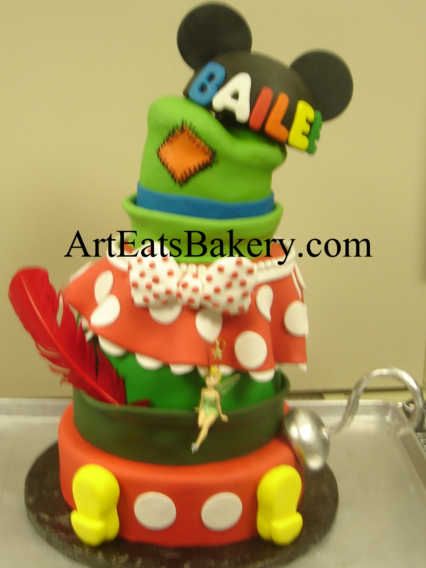 Mickey's pants and Minnie Mouse skirt, Goofy's, Peter Pan's and mouse ears hats mad hatter sweet sixteen birthday cake design with edible Captain Hook's hook, polka dot bow, and Mickey's feet.jpg
