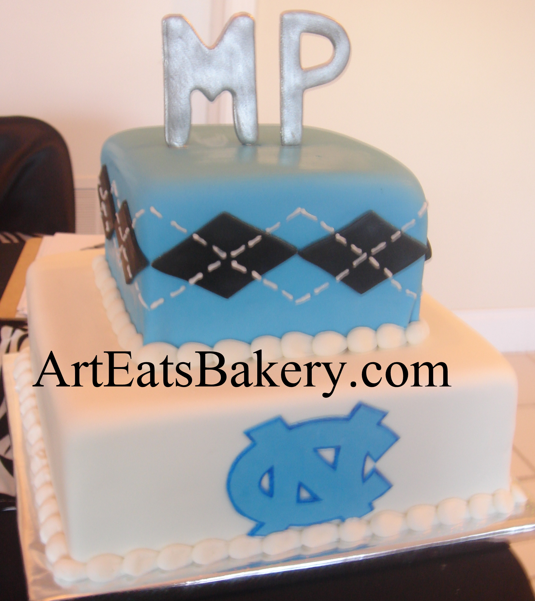 Two tier square blue, white and black men's creative custom University of North Carolina logo birthday cake design with silver monogram topper.jpg