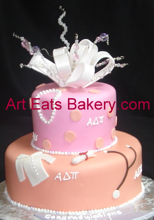 Two tier orange and pink fondant Clemson cake with lab coat, diploma, stethoscope, pearls, bow and crystal topper.jpg