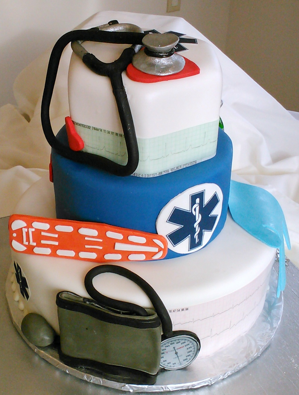 EMT Parametics three tier custom wedding cake with edible blood pressure cuff, glove, hearts, back board, Stethoscopes and oxygen tank. The Bride and Groom's heart beats are on edible EKG paper.jpg