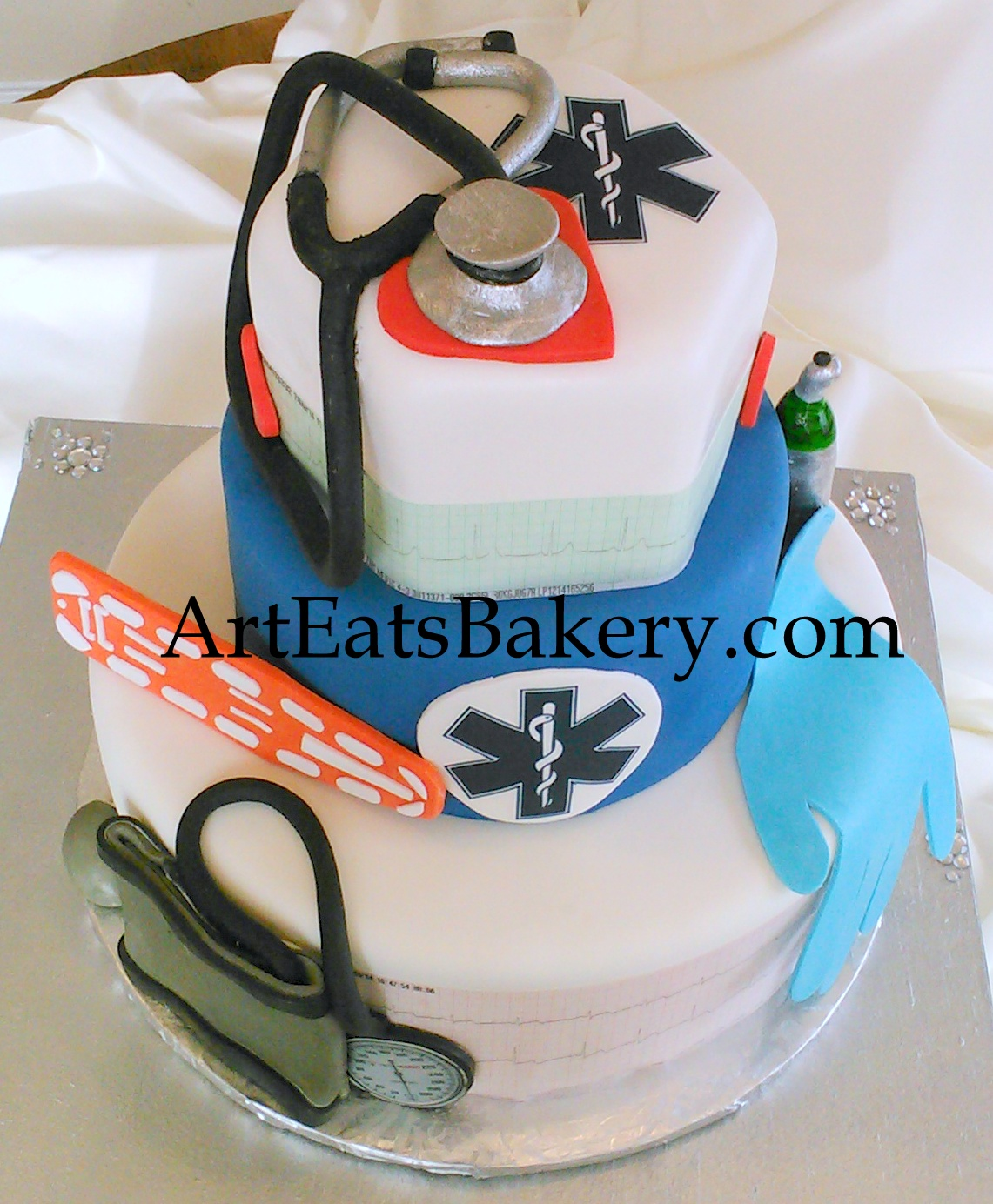 EMT Parametics three tier custom wedding cake with edible blood pressure cuff, glove, hearts, back board, Stethoscopes and oxygen tank.jpg