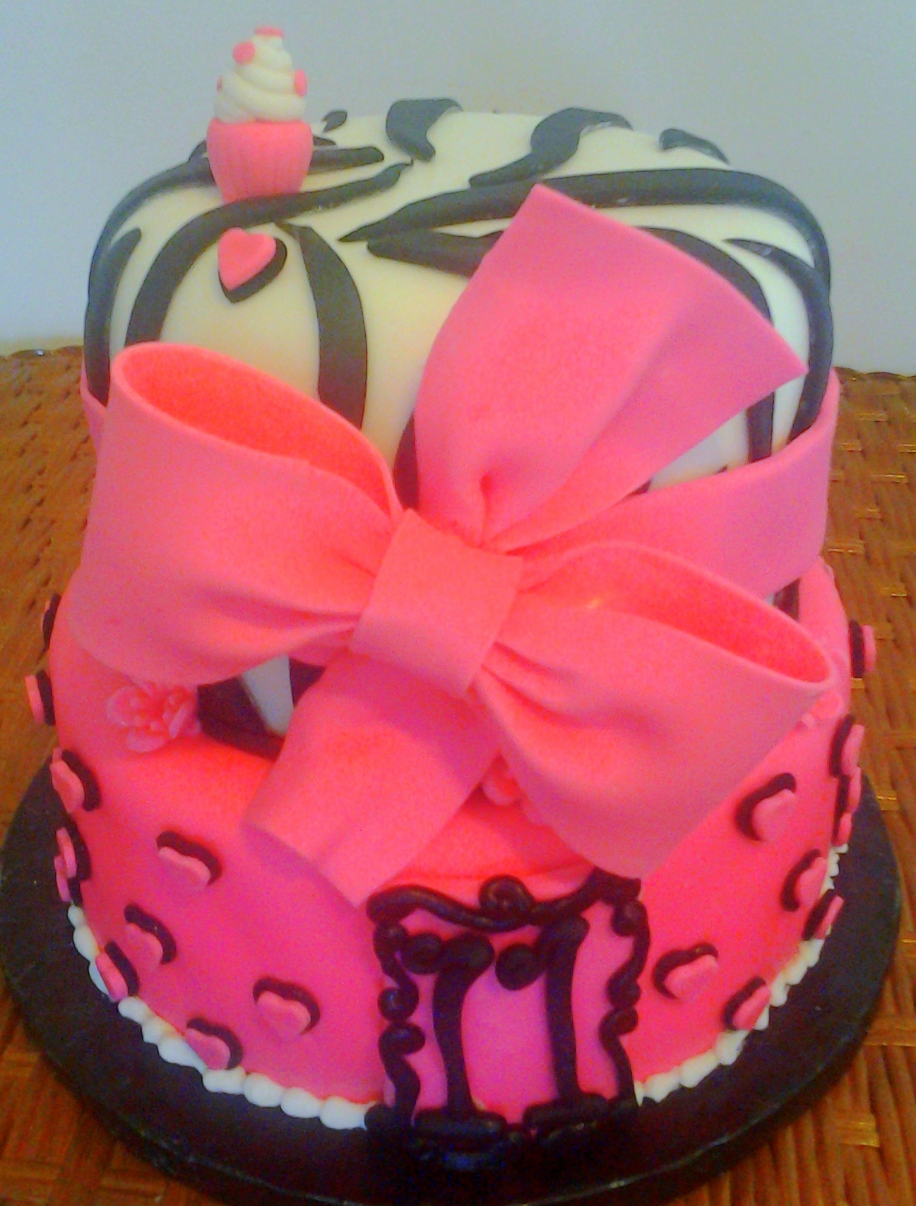 Girl's two tier animal print zebra stripe and hearts pink and black fondant modern 11th birthday cake design with edible bow.jpg
