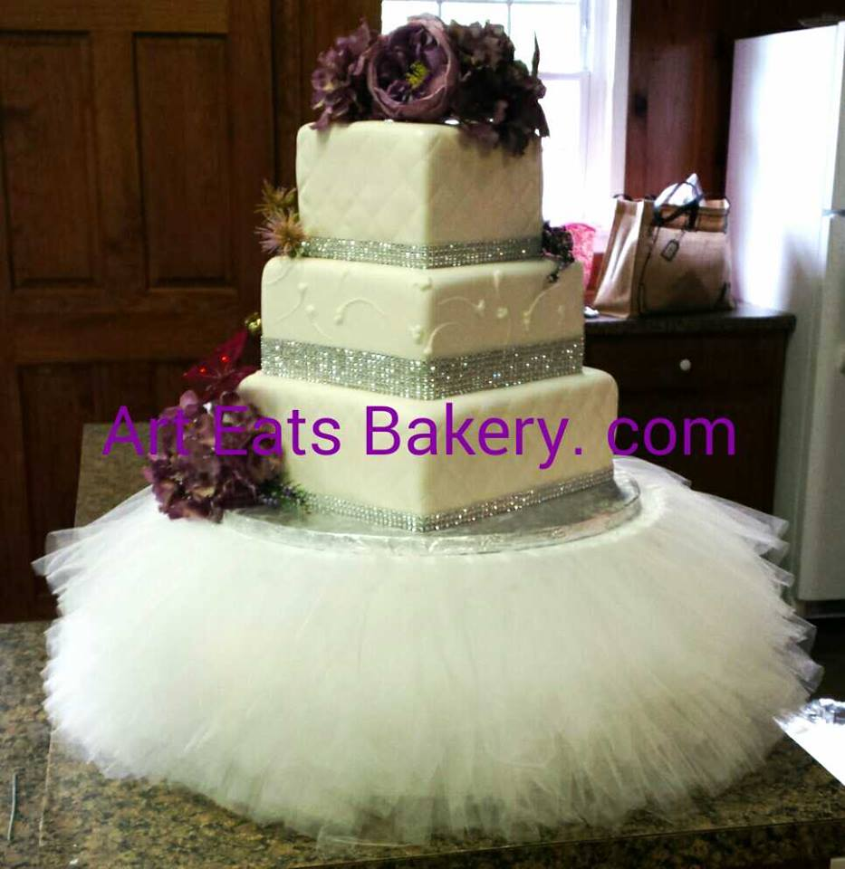 Three tier custom designed unique white fondant wedding cake with diamond embossing and fabric stand.jpg